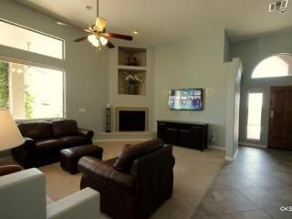 Spacious sunny living room with a gas fire place and wall mounted flat screen TV