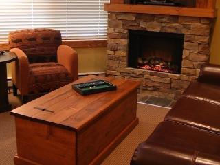 The living area has a cozy feel with a glowing fireplace and comfy furniture.