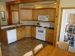 The open-plan kitchen features a 6 person dining table and a private balcony with BBQ